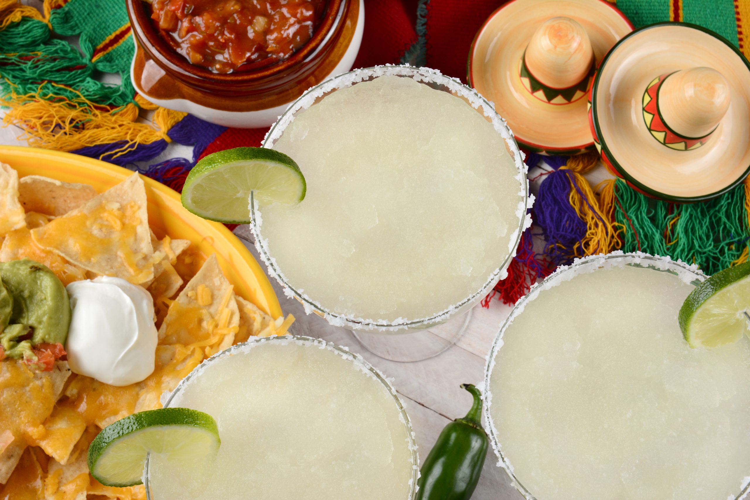 High angle view of three margarita cocktails surrounded by nachos, chips and salsa on a bright Mexican, table cloth. Horizontal format. Perfect for Cinco de Mayo projects.